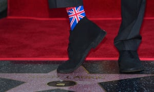 Hugh Laurie shows off his socks while standing on his just unveiled Star during his Hollywood Walk of Fame star ceremony.