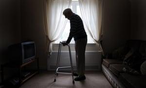 Pensioner leaning on walking frame