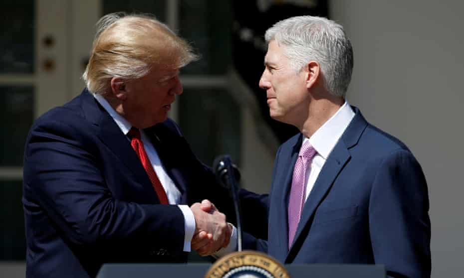 Donald Trump shakes hands with Judge Neil Gorsuch after he was sworn in as a supreme court justice.