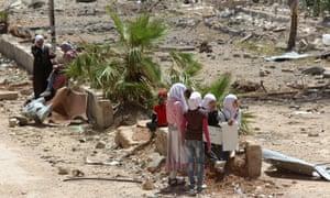 Syrian girls sit holding placards in Darayya.