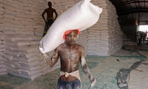 An aid worker carries a sack of flour in the northern province of Hajjah on September 25, 2018, as Yemenis displaced from the port city of Hodeidah receive humanitarian aid donated by the World Food Programme (WFP).
