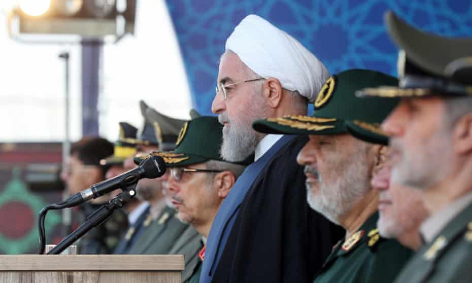 Iranian president Hassan Rouhani, centre, watches the annual military parade where he gave his speech