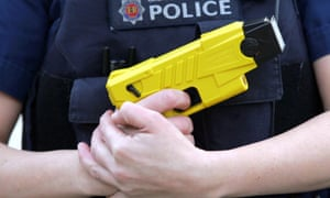 A police officer holding a Taser weapon