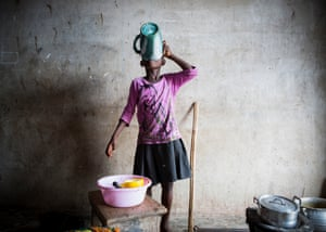 In Nyanyano a young girl prepares food for her family using pots and pans covered in flies