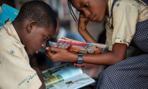 A boy and a girl sit and read books in a mobile library in Lagos.
