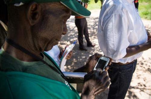 A Wash community champion enters data on to a simple Nokia phone, which will then be collected on a central server for analysis, in Zambia.