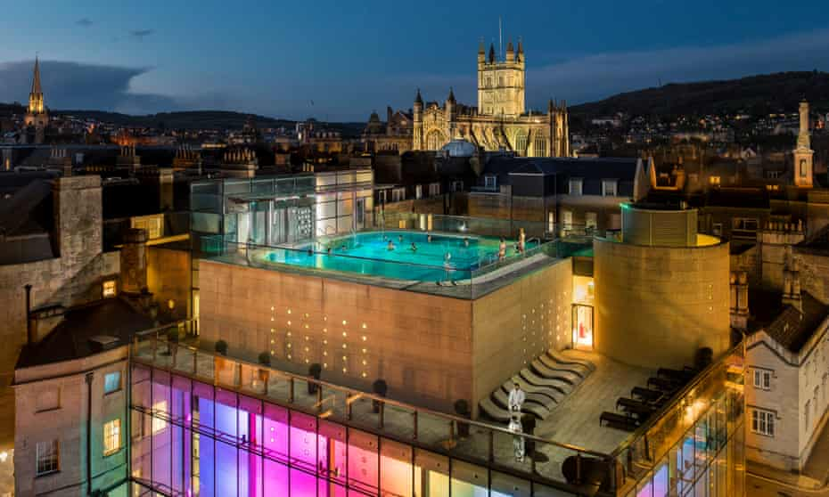 Aerial view of outdoor pool at Thermae Bath Spa by night, Bath, Somerset, with cathedral in background