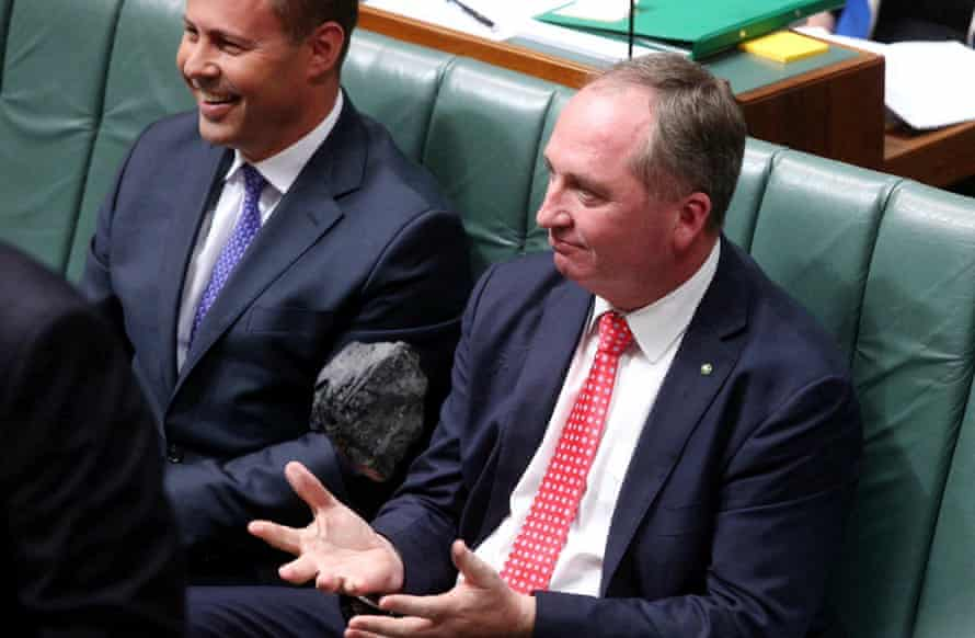 Josh Frydenberg sitting next to Barnaby Joyce, who is tossing a piece of coal in parliament.