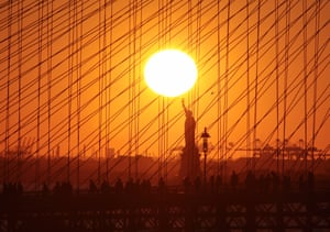 New York, US Pedestrians cross the Brooklyn Bridge as the sun sets behind the Statue of Liberty