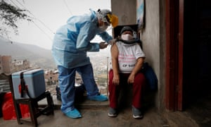 A nurse from the Cerro El Agustino medical post gives a resident flu and pneumonia vaccines, in Lima, Peru.