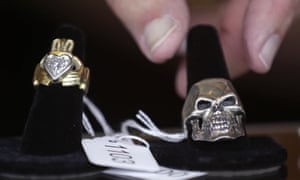 Auctioneer Bob Sheehan reaches for a silver skull ring, which is on display next to a diamond claddagh ring,.