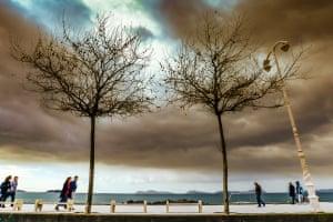 Calm before the StormPeople walking along the boardwalk at Samil beach in Vigo Photograph: Olivier Guiberteau/GuardianWitness
