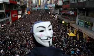 A protester wearing a Guy Fawkes mask looks out over a sea of people marching in Hong Kong on Sunday.