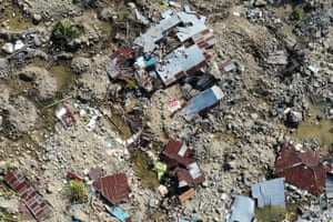 Survivors salvage useable items from the debris of a destroyed house in Palu.