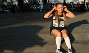 Luz pulls on a pair of headphones while recording a rap video in the main plaza in Ecatepec.