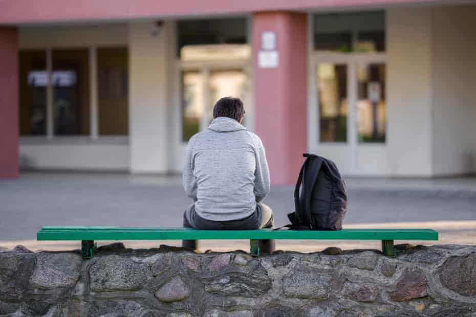 One young man sitting on bench at school yard.
