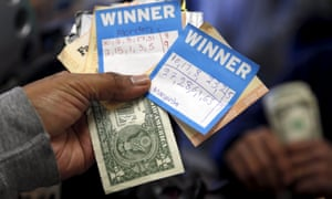 A man holds Powerball lottery ticket numbers chosen by his wife and daughters at Bluebird Liquor in Hawthorne, Los Angeles, on Tuesday.