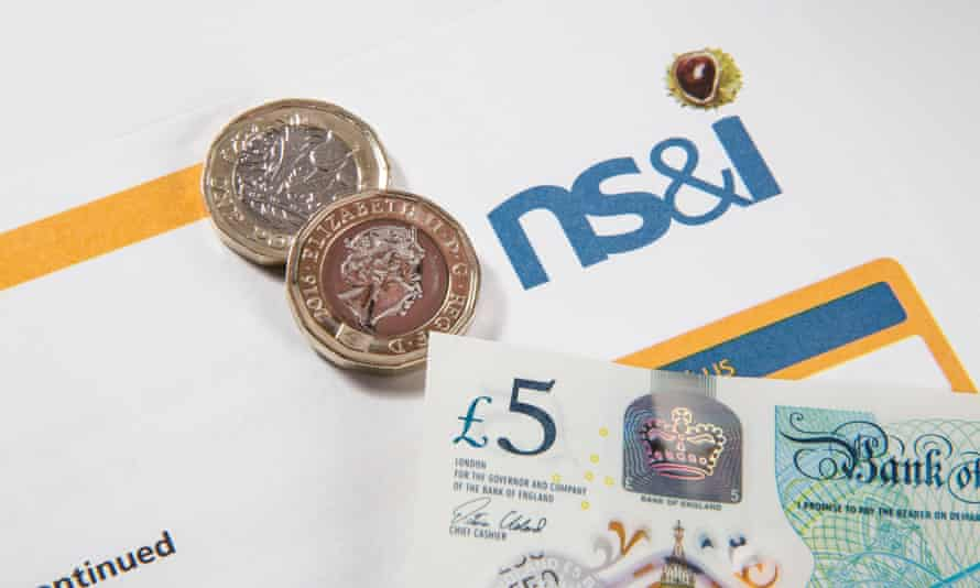 Two new pound coins on an NS&I savings bond