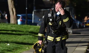 A firefighter reacts after battling a huge blaze at the Grenfell Tower.