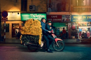 A delivery driver on a motorbike in Hanoi, Vietnam, carrying flowers