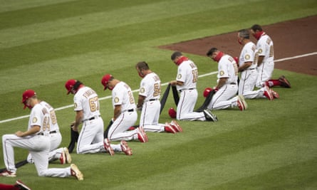 Members of Washington Nationals kneel and hold a piece of black fabric before an opening day baseball game against the New York Yankees at Nationals Park, Thursday.