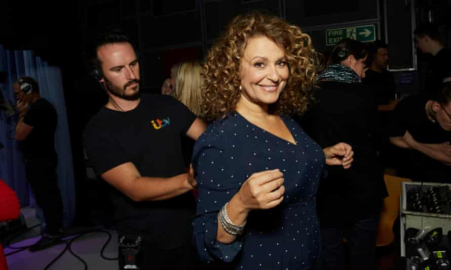 Nadia Sawalha smiling and with her shoulders back as a technician, standing behind her, wires her for sound