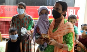 Indian women and children wearing face masks wait for coronavirus tests at a hospital in Jammu.