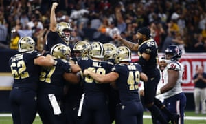 Wil Lutz is swamped by his teammates after clinching the game for the Saints