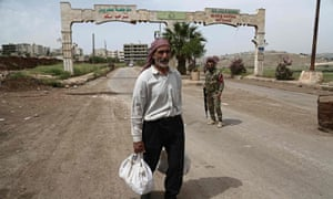A Syrian man walks away from the entrance to Afrin.