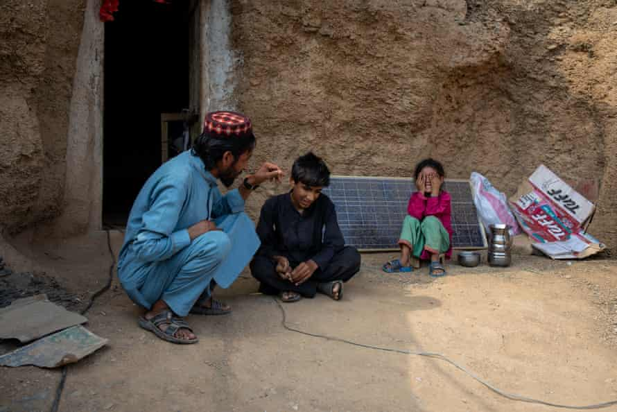 Janas Khan jokes with his son and daughter outside their cave home