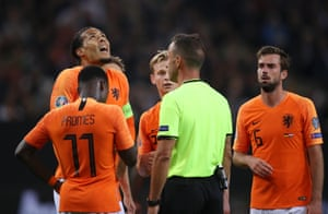 Virgil Van Dijk and teammates confront referee Artur Soares Dias after he awards Germany a penalty.