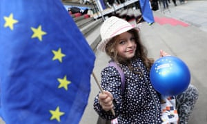 A child waves an EU flag and holds a balloon with the EU stars on it