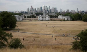 Canary Wharf seen from the dried-out grass of Greenwich Park.