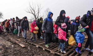Migrants and refugees walk over wooden pallets after crossing into Serbia via the Macedonian border.