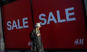 A person walks past a massive sale sign in the window of H&M