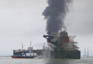 A tugboat attempts to extinguish a fire on an oil tanker