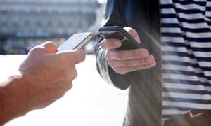 Two men exchanging information via smartphone