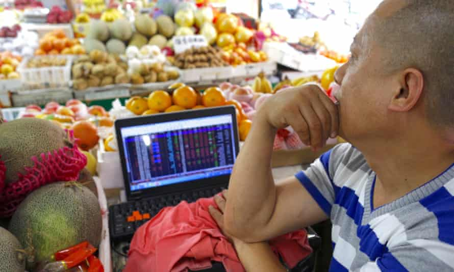 A fruit seller checks Chinese stock prices on his computer in a market in Hangzhou, Zhejiang province.