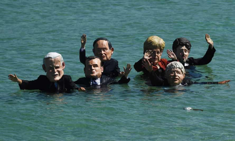 Aktivis Extinction Rebellion yang mengenakan topeng pemimpin G7 berdemonstrasi di laut lepas St Ives, Inggris
