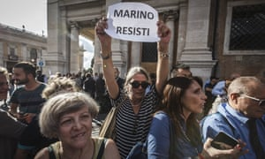 A pro-Marino demonstrator holds a placard reading 'Marino resist' during a rally outside Rome's city hall.