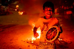 A boy plays a drum beside a bonfire in Chennai, India