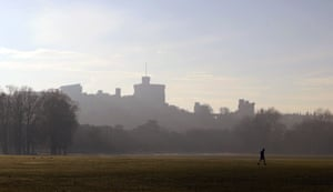 A runner crosses the public sports fields of Home Park as fog surrounds the distinctive silhouette of Windsor Castle in Berkshire