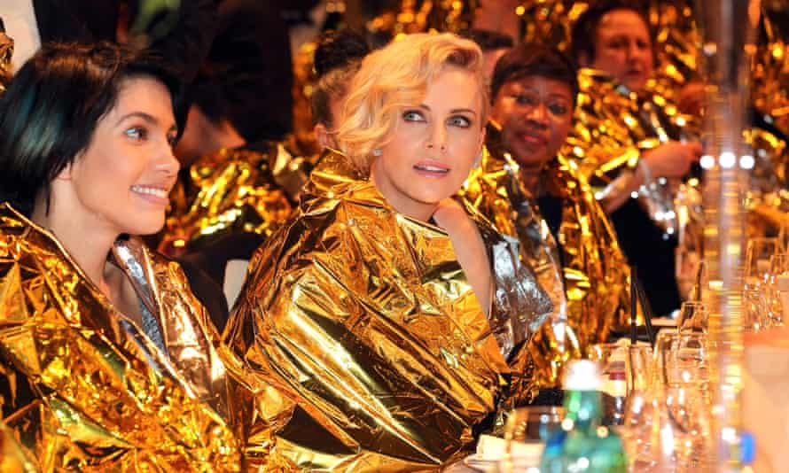 The actor Charlize Theron sits wrapped in an emergency blanket alongside Nadya Tolokonnikova at the Cinema for Peace event.