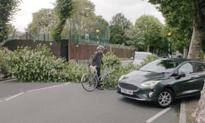 A cyclist and cars try to get around a fallen tree across the road in west London