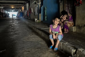 Children sit in the near-darkness of a derelict factory, Saida