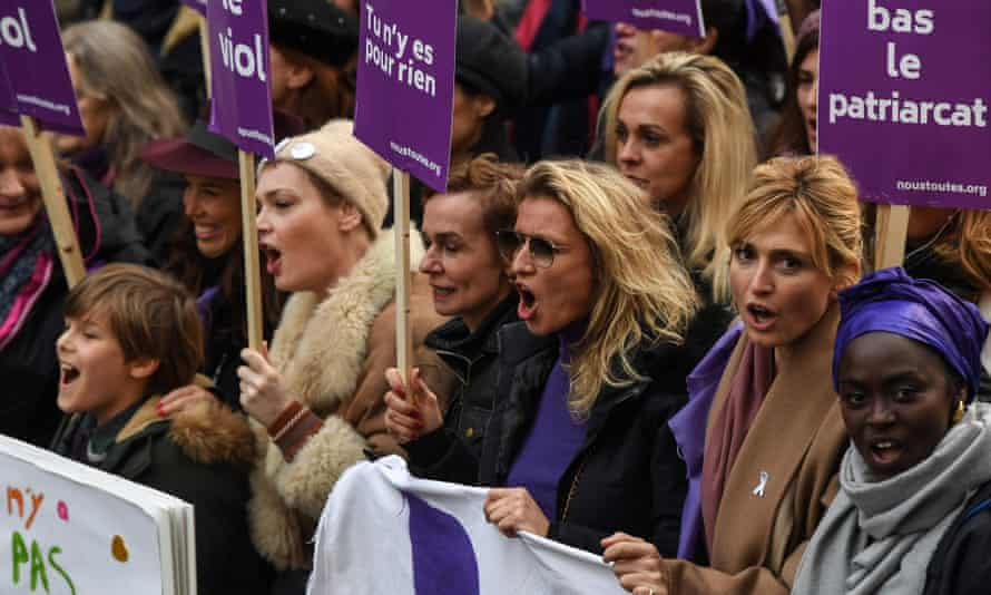 French actress Julie Gayet (2R) and French actress Alexandra Lamy (3R) near banners reading 'Down with the patriarchy'.