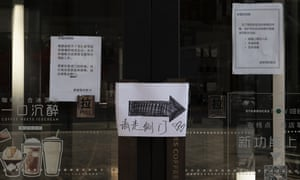 Notices on a Starbucks, which is temporarily closed down, say consumer must have their body temperatures checked, disinfect hands, and wear masks before entering the coffee shop.