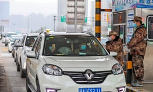 A militia member checks the body temperature of a passenger on a vehicle at an expressway toll gate in Wuhan, Hubei province, on Thursday.
