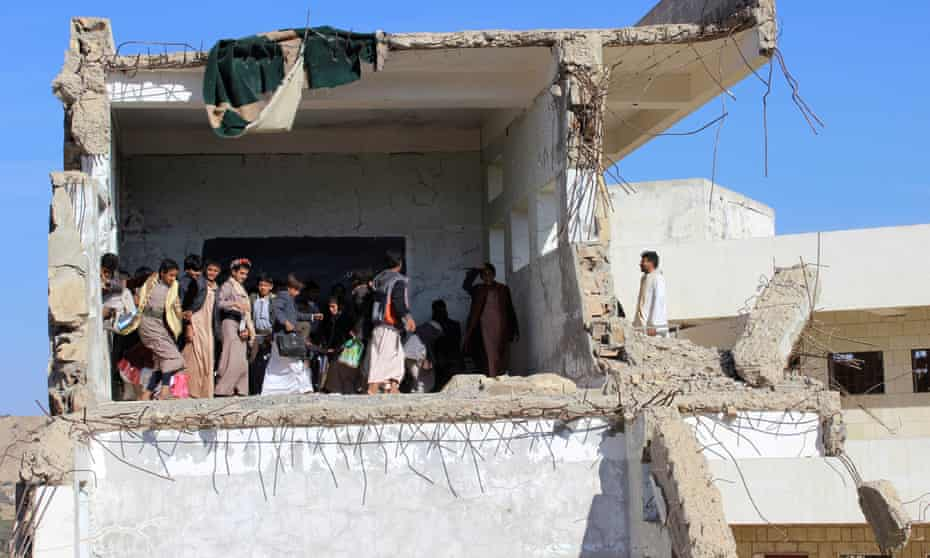 Yemeni students gather inside a class at their school, which was recently hit by a Saudi-led air strike.