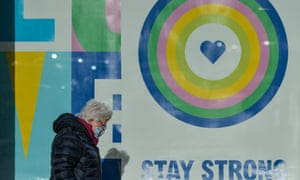 A woman wearing a face mask walks by a poster in a shop window in Dún Laoghaire, south Dublin.